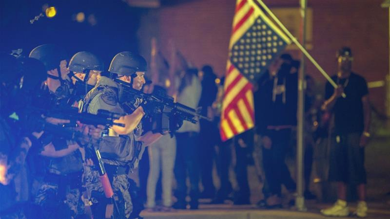 A police officer raises his weapon at a speeding car during protests in Ferguson, Missouri in August 2014 [Lucas Jackson/Reuters]