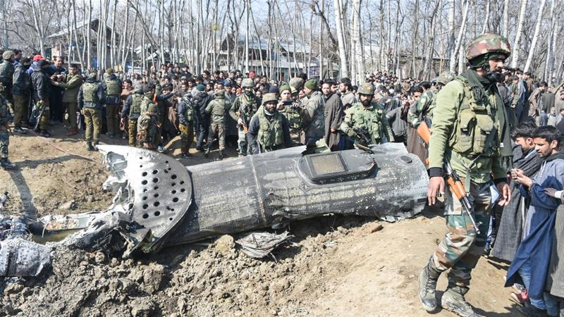 Indian soldiers and onlookers stand near the remains of an Indian Air Force aircraft after it crashed in Indian-administered Kashmir [Tauseef Mustafa/AFP]