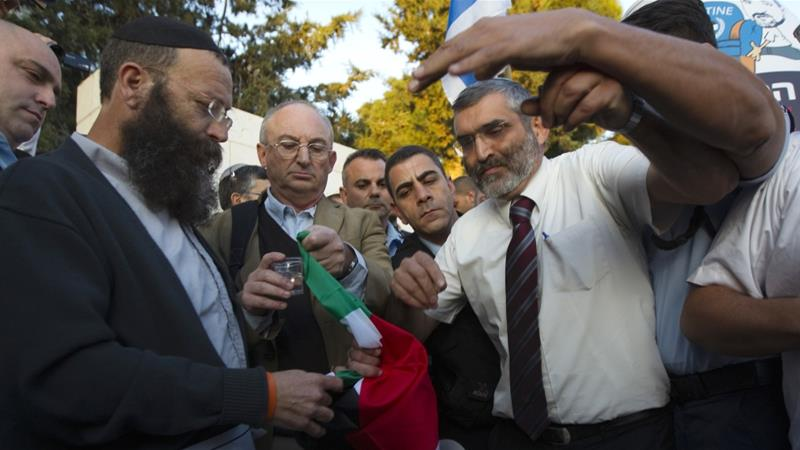 Otzma Yehudit leader Michael Ben Ari stands next to far-right protesters as they burn a Palestinian flag during a demonstration in the West Bank on November 29, 2012 [File: Ronen Zvulun/Reuters]
