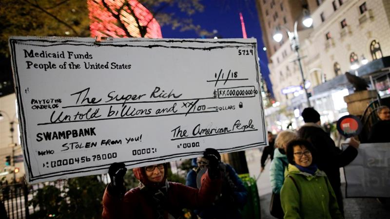 File: Demonstrators take part in a protest against tax cuts for rich people in the Manhattan borough of New York City,US November 27, 2017 [Eduardo Munoz/Reuters]