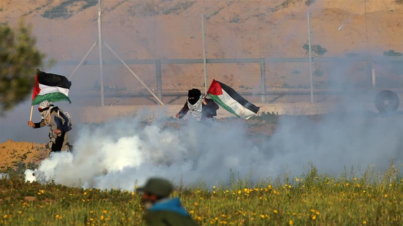 Women holding Palestinian flags run from tear gas fired by Israeli forces during a protest at the Israeli fence east of the Gaza Strip [Ibraheem Abu Mustafa/Reuters]