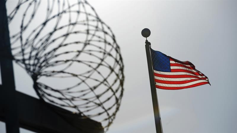 FILE: A US flag flies above a razorwire-topped fence at the 'Camp Six' detention facility at US Naval Station Guantanamo Bay December 10, 2008 [File:Mandel Ngan/Reuters]
