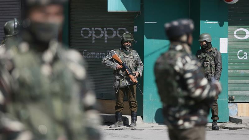 Indian soldiers stand guard outside a market in Kashmir's Srinagar city [Mukhtar Khan/AP]