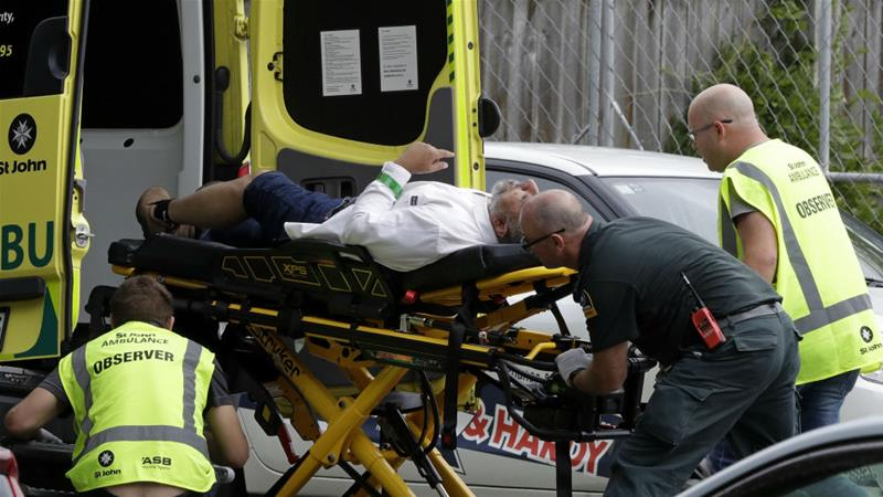 Ambulance staff take a wounded man from outside the mosque in central Christchurch on Friday [Mark Baker/AP]