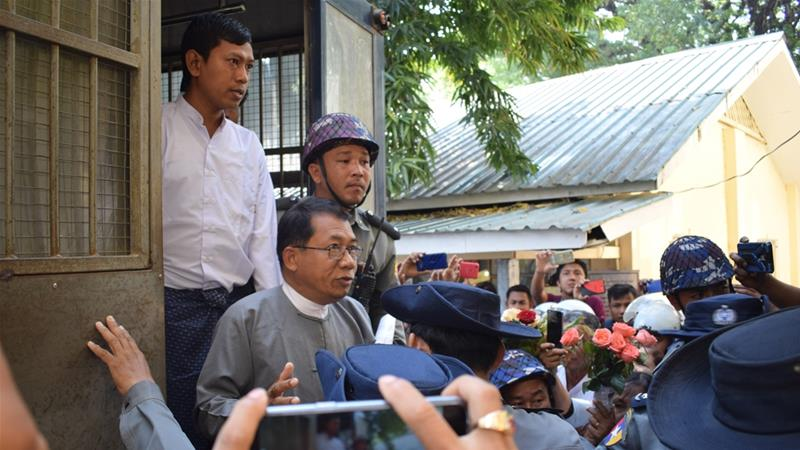 Aye Maung, centre, former Arakan National Party leader, speaks to the media while being escorted out of court by police officers after his hearing [AFP]
