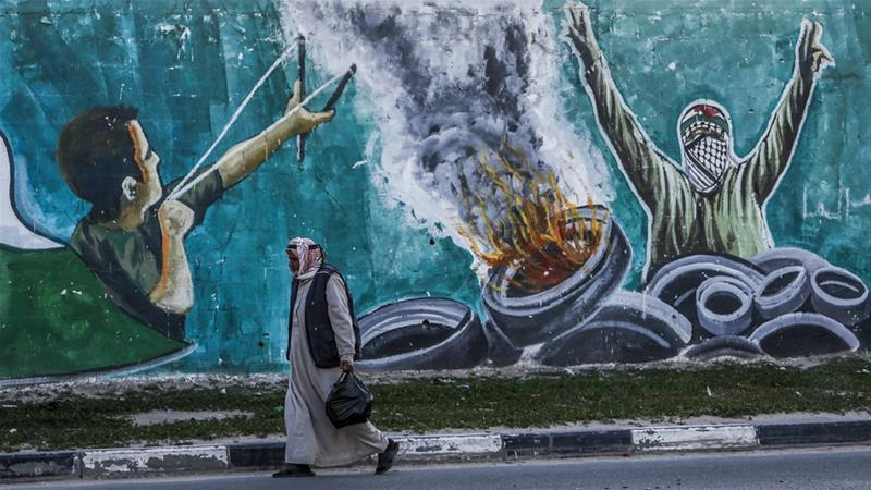 A Palestinian man walks past a mural in a street in Rafah in the southern Gaza Strip [Said Khatib/AFP]