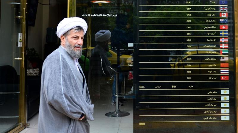 A man walks past an exchange bureau in Tehran, Iran [File: Fatemeh Bahrami/Anadolu Agency]