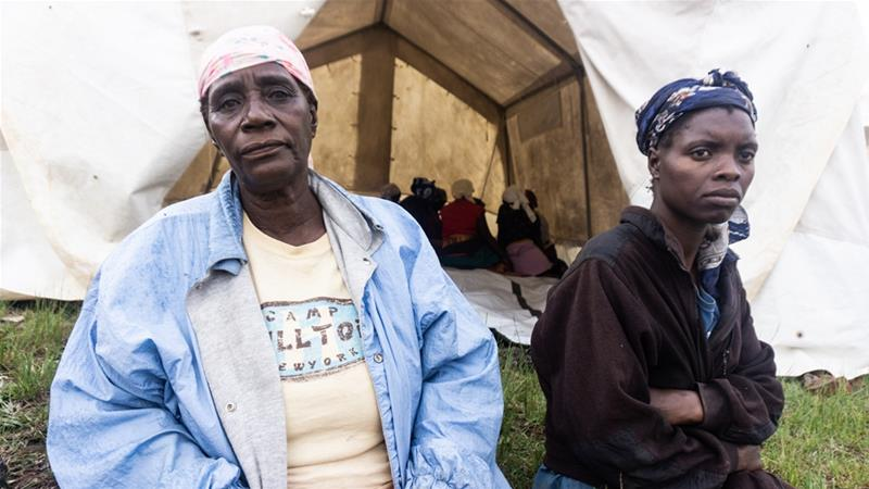 Rose Mukamba and a neighbour wait to receive medical attention at the temporary medical relief centre at Skyline [Tendai Marima/Al Jazeera]