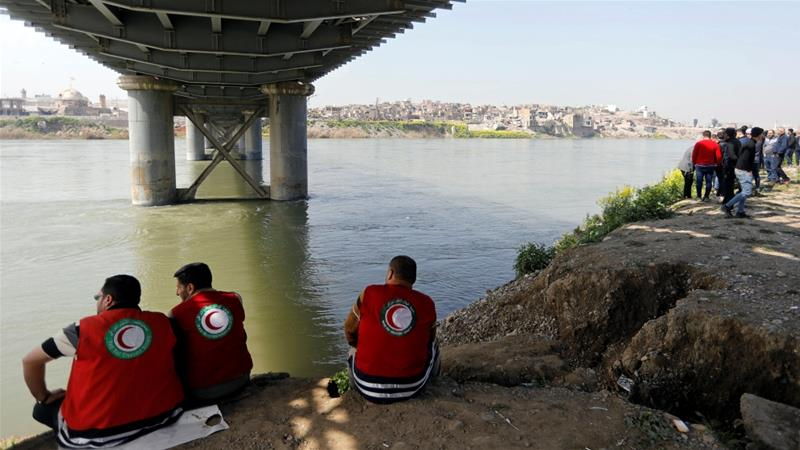 Iraqi rescue team members rest near the site where the ferry sank in the Tigris River in Mosul last week [Khalid al-Mousily/Reuters]