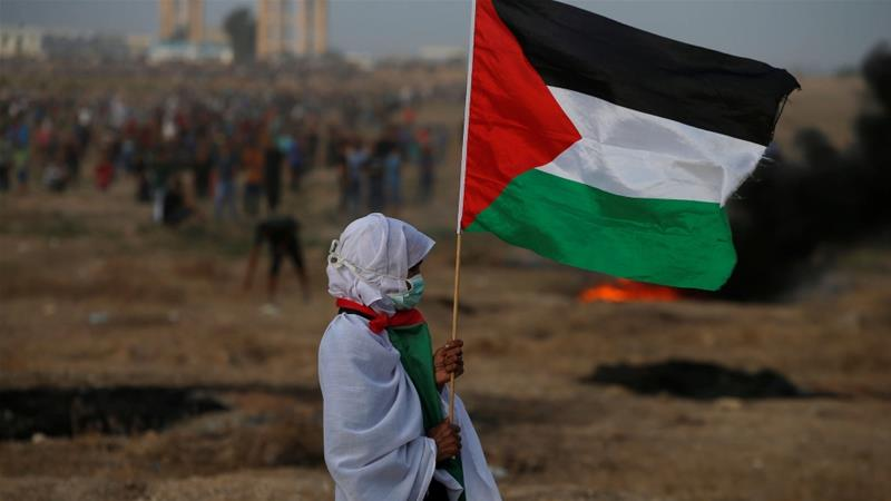 A woman holds a Palestinian flag during a protest demanding the right to return to their homeland, at the Israel-Gaza border fence in Gaza October 19, 2018 [File: Mohammed Salem/Reuters]