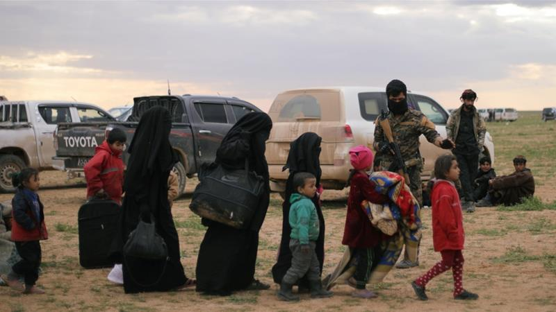 Relatives of ISIL fighters walk near the village of Baghouz, in Syria's Deir Az Zor province, in February [Rodi Said/Reuters]