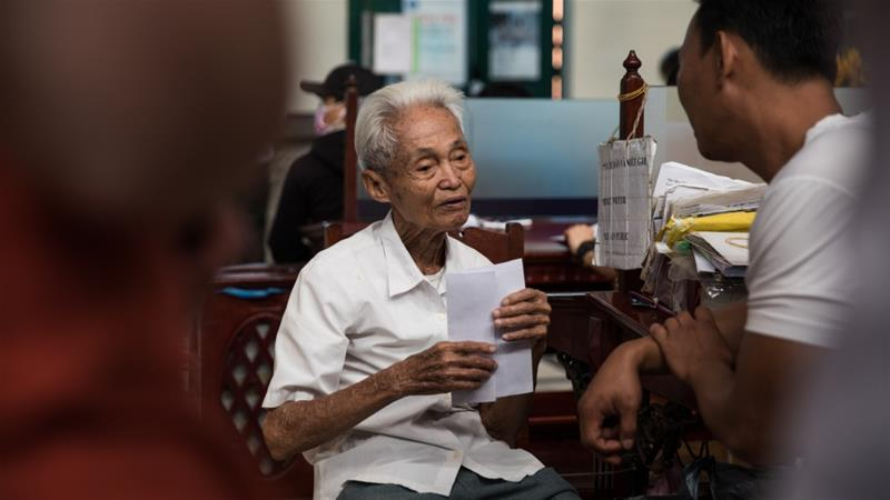 A group of foreign tourists and their Vietnamese tour guide talk to Duong Van Ngo, 89, at the Saigon Central Post Office [Valerie Plesch/Al Jazeera]