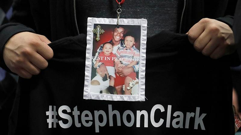 A mourner holds up a photo of police shooting victim Stephon Clark during the funeral services for Clark at Bayside Of South Sacramento Church March 29, 2018 in Sacramento, California [File: Jeff Chiu-Pool/Getty Images]