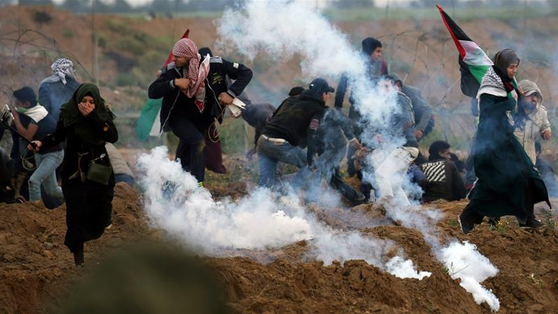 Palestinian demonstrators run away from teas gas fired by Israeli forces during a protest at the Israeli fence in the southern Gaza Strip [File: Ibraheem Abu Mustafa/Reuters]