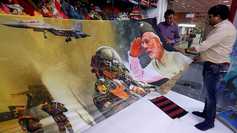 Traders in India's Surat city display a sari, traditional clothing for women, with printed images of Prime Minister Modi and Indian Army [Amit Dave/Reuters]