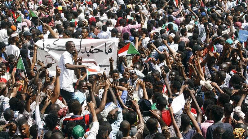 Sudanese demonstrators gather in a street in central Khartoum to celebrate al-Bashir's removal [Ashraf Shazly/AFP]