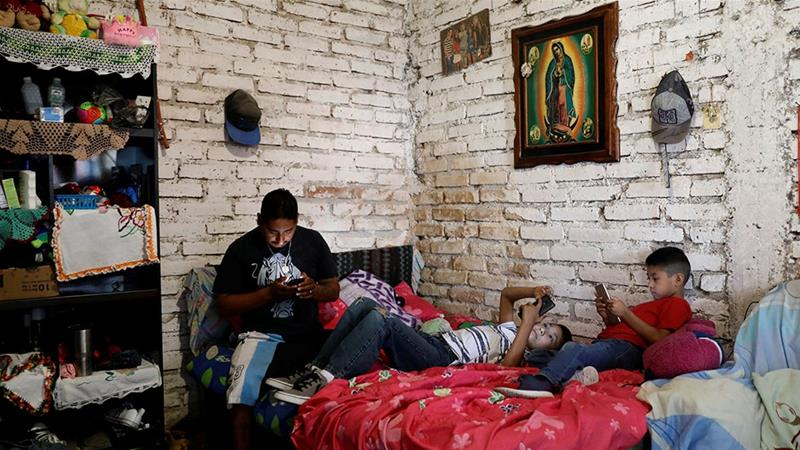 Balbino, 33, a Mexican migrant, who was denied a visa to the US, looks at his mobile phone next to his sons Juan, 10, and Javen, 6, inside their house in Neutla, Guanajuato state, Mexico [Edgard Garrido/Reuters]