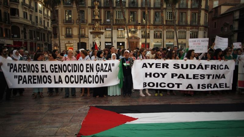 People hold banners saying 'Stop the genocide in Gaza. Stop the occupation' and 'Yesterday South Africa, today Palestine. Boycott Israel' at a protest in Malaga, Spain on July 17, 2014 [File: Reuters]
