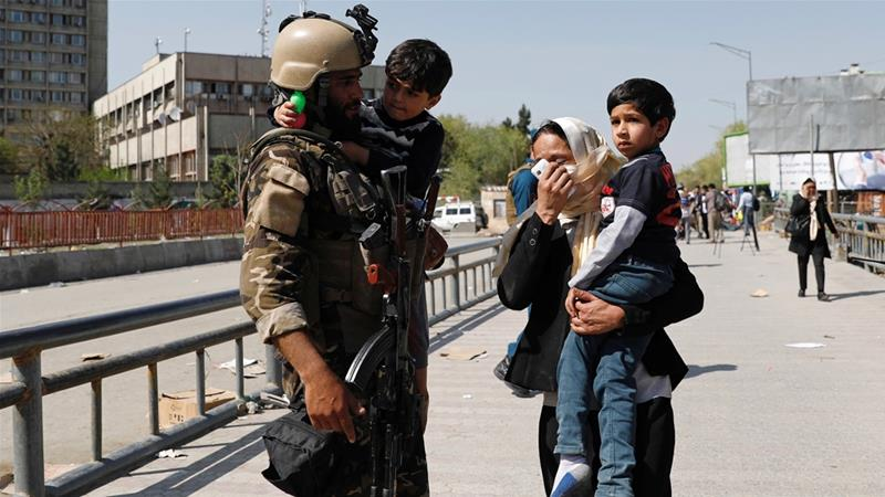 Rescued children are carried from the site of Saturday's attack in Kabul [Mohammad Ismail/Reuters]