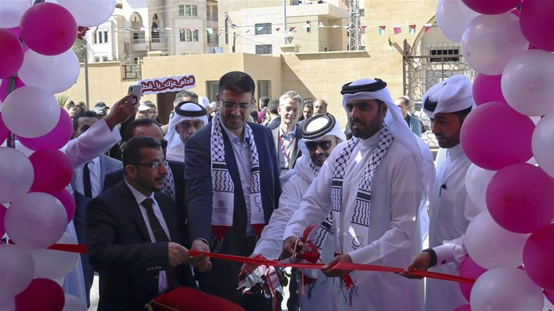 Khalifa al-Kuwari, director of the Qatar Fund for Development, cuts the ribbon during the opening ceremony [Adel Hana/AP]