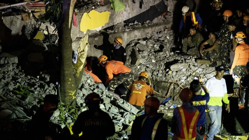Rescue workers search through rubble in Porac after earthquakes struck on Monday [Noel Celis/AFP]