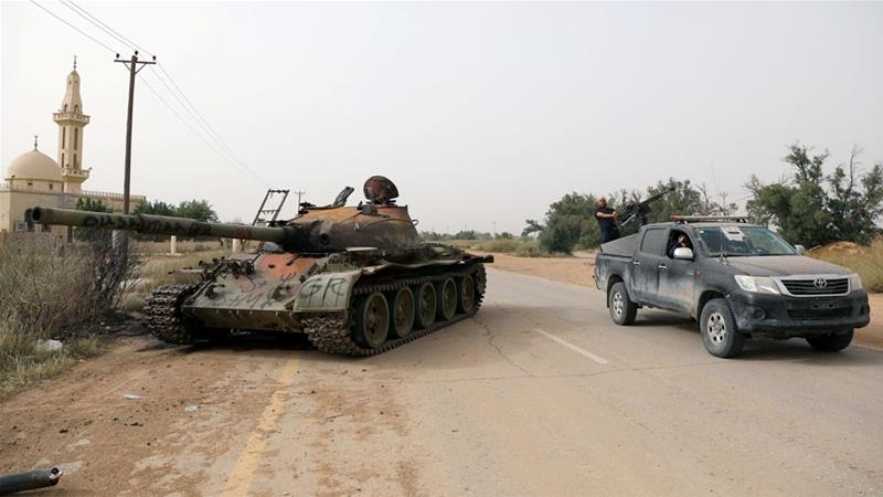 Members of Libyan internationally recognised government forces pass near a damaged tank belonging to eastern forces in Al Hira area, southwestern Tripoli [Hani Amara/Reuters]
