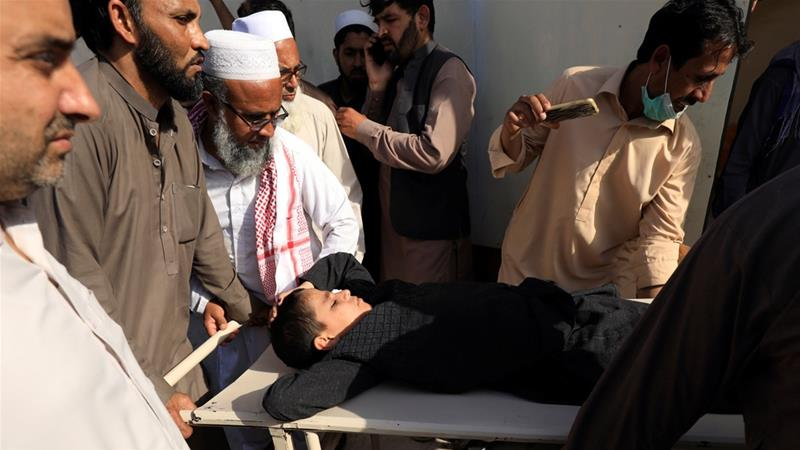 People move a child on stretcher after what they say was a defective polio vaccine administered outside a hospital in Peshawar on Monday [Fayaz Aziz/Reuters]