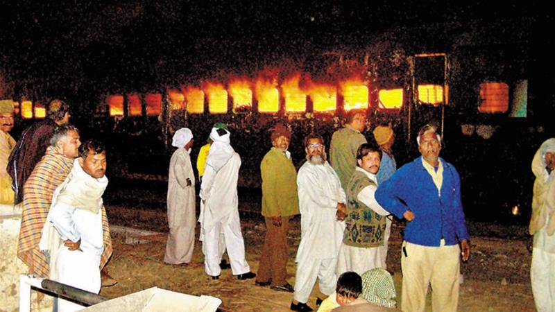 Survivors look on as the compartments of Samjhauta Express burn after an explosion at Dewana village in India, on February 19, 2007 [File: AP/Dainik Bhaskar]