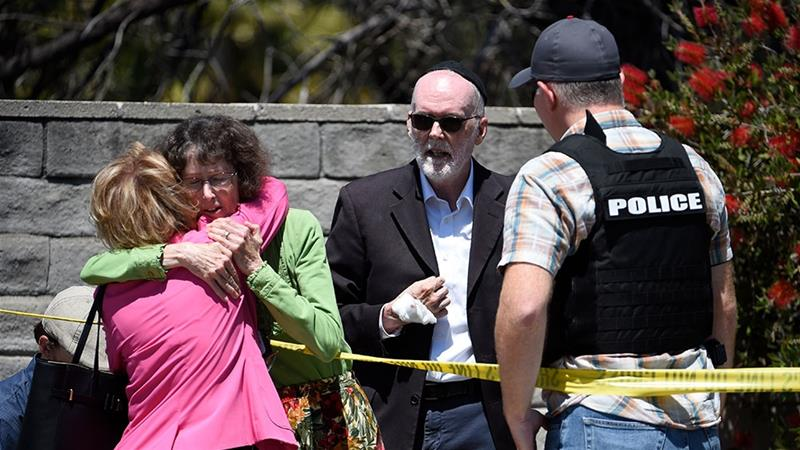 Two people hug as another talks to a San Diego County Sheriff''s deputy outside of the Chabad of Poway synagogue [Denis Poroy/AP Photo]