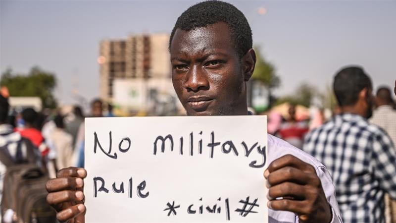 A protester holds a placard during a sit-in outside the army headquarters in the capital Khartoum on Monday [Ozan Kose/AFP]