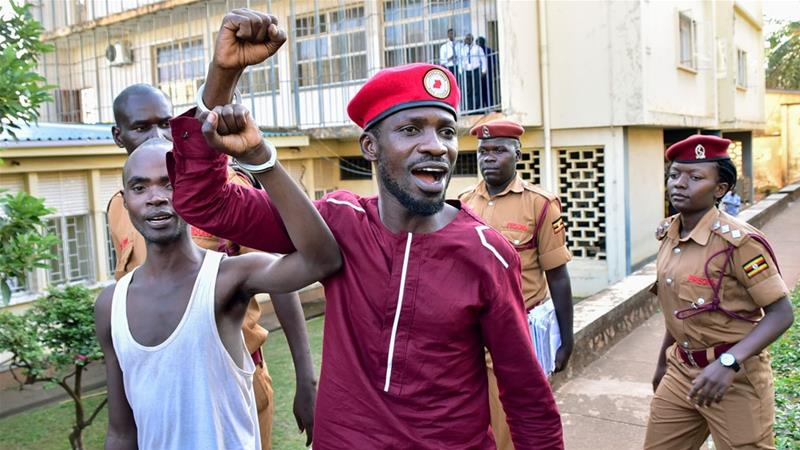 Opposition figure Bobi Wine walks handcuffed with another prisoner before boarding a bus to Luzira prison last month [AFP]