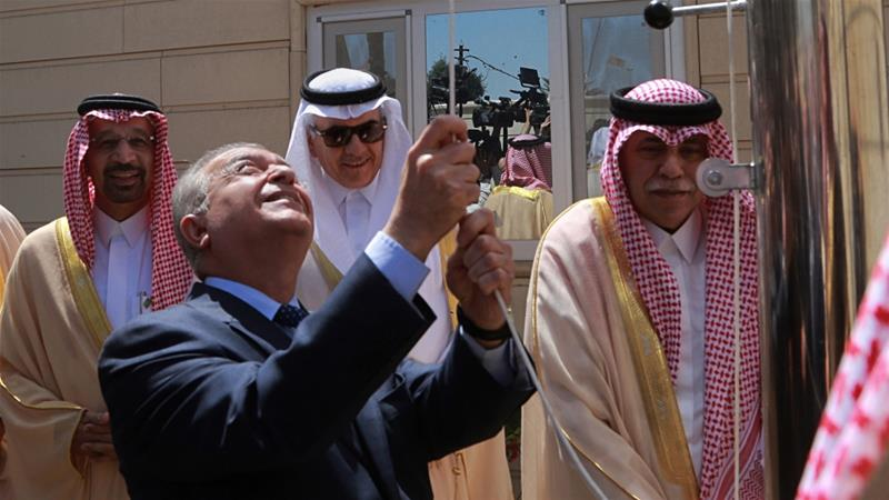 Iraq's Foreign Minister Mohamed Alhakim, centre, raises the Saudi flag during the opening ceremony of the kingdom's consulate in Baghdad [Hadi Mizban/AP]
