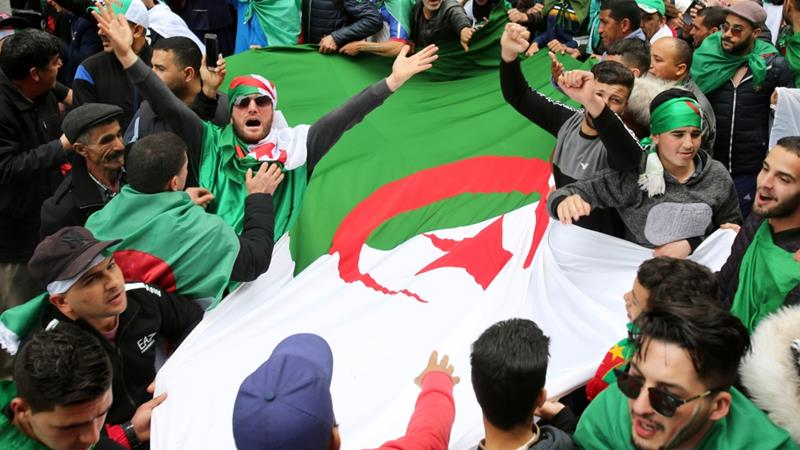 People in Algiers carry an Algerian flag during a protest to push for the removal of the current political structure [Ramzi Boudina/Reuters]