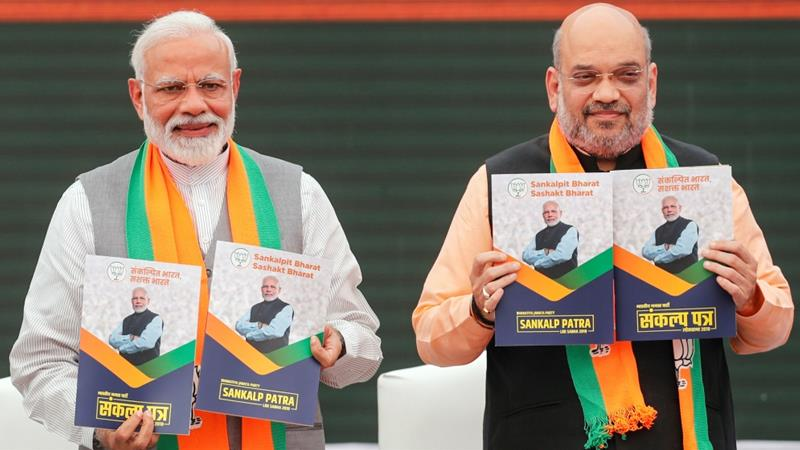 Indian Prime Minister Modi and chief of the ruling party Amit Shah display copies of their party's election manifesto [Adnan Abidi/Reuters]
