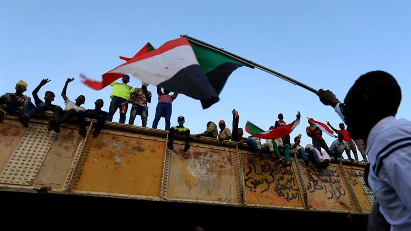 A demonstrator waves a Sudanese national flag from atop a bus as he arrives to join a mass rally in Khartoum [Mohamed Nureldin Abdallah/Reuters]