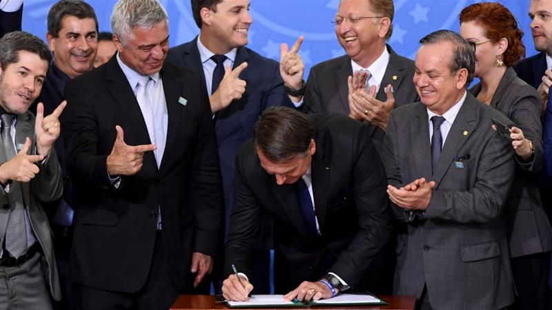 Bolsonaro, who had already issued a decree in January to make it easier to own a gun, signed the May 7 order surrounded by supporting legislators [Evaristo Sa/AFP]