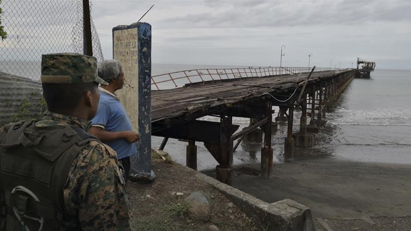 A police officer and resident look out at an abandoned pier in Puerto Armuelles after the quake made the structure at the end incline to the right