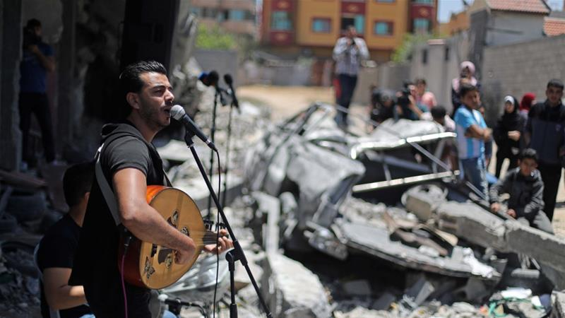 A Palestinian singer performs during an event calling for the boycott of Eurovision on the rubble of a building recently destroyed by Israeli air raids in Gaza on May 14 [Reuters/Mohammed Salem]