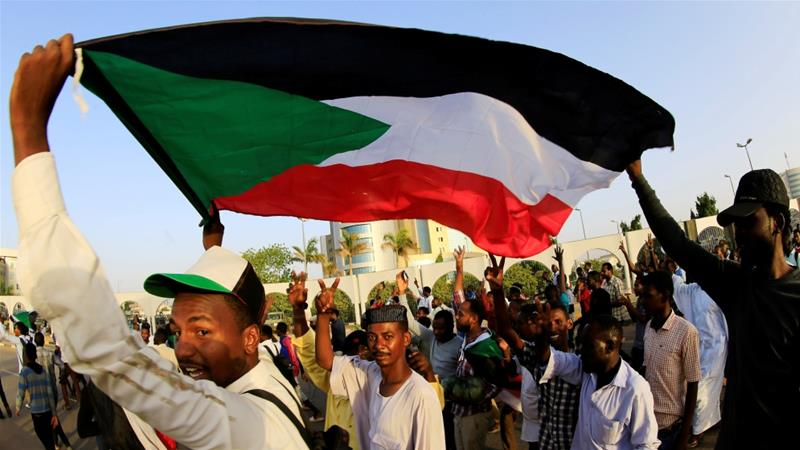 Sudanese protesters carry their national flag as they chant slogans in front of the Defence Ministry compound in Khartoum [Mohamed Nureldin Abdallah/ Reuters]