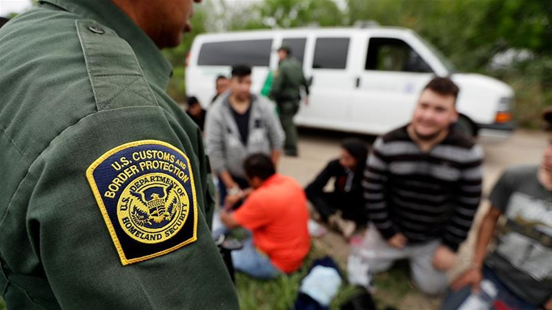 A Border Patrol agent talks with a group suspected of having entered the US near McAllen, Texas [File: Eric Gay/AP Photo]