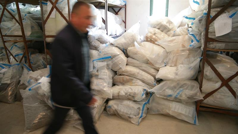 An Albanian police officer walks past a huge stash of confiscated narcotics in storage outside Tirana [Vincent Triest/Al Jazeera]