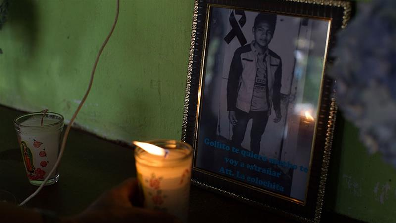 Bartolome Hernandez places a candle in front of a photo his son, Carlos Gregorio Hernandez Vasquez, in the family''s home in San Jose El Rodeo [Jeff Abbott/Al Jazeera]