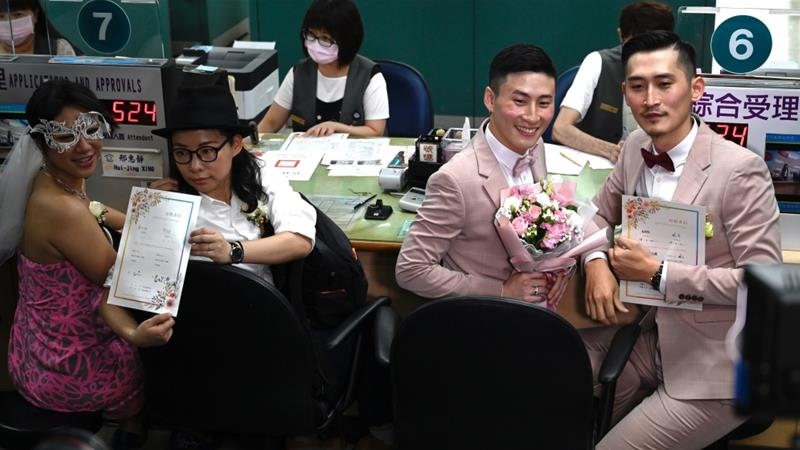 The first two couples to register in Taipei display their wedding certificates [Sam Yeh/AFP]