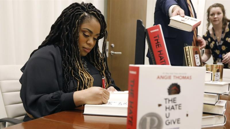 Author Angie Thomas signs a copy of her best-selling young adult novel, The Hate U Give [File: Rogelio V. Solis/ AP Photo]