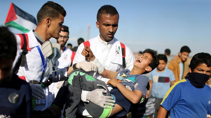 A wounded Palestinian boy is evacuated during a protest at the Israel-Gaza fence, in the southern Gaza Strip on May 3, 2019 [Reuters/Ibraheem Abu Mustafa]