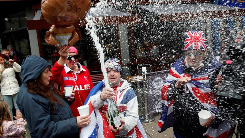 Fans celebrate the announcement of the birth of the newest British royal family member on Monday [Adrian Dennis/AFP]