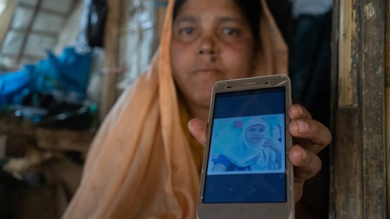 Hamida holds up a picture of her 15-year-old daughter-in-law, who was brought from Myanmar and into Bangladesh and then smuggled to Malaysia to marry her son [Kaamil Ahmed/Al Jazeera]
