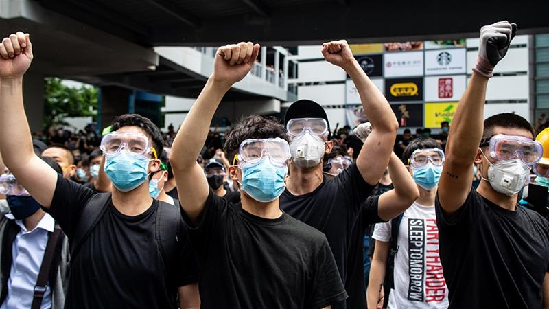 Protesters in masks and goggles chant slogans outside the Legislative Council in Hong Kong on June 12 [Philip Fong/AFP]