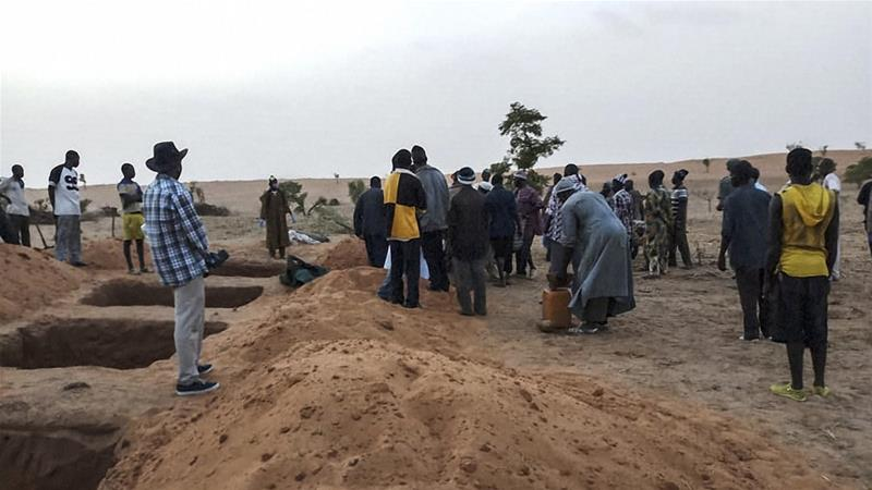 Officials and residents stand near freshly dug graves in the Dogon village of Sobane-Kou after the attack [File: AFP]