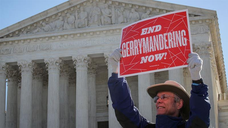 A demonstrator holds a sign during a Fair Maps rally outside the US Supreme Court [File: Brendan McDermid/Reuters]